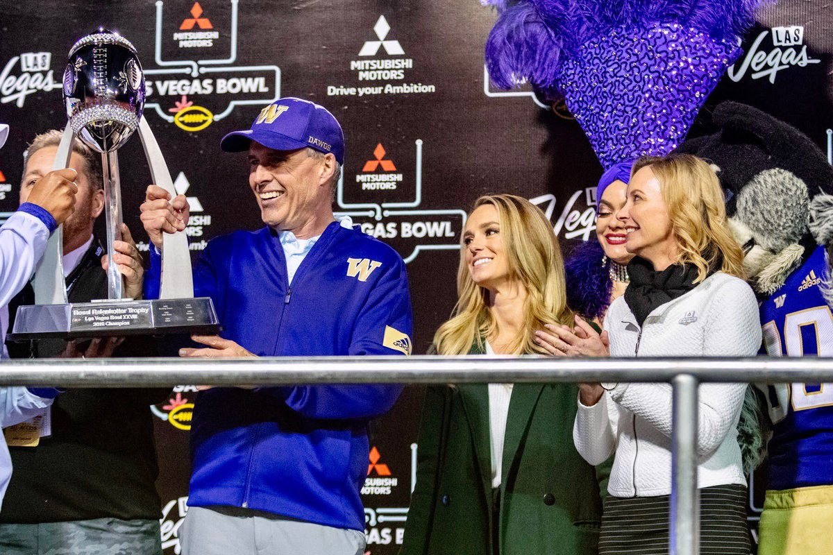 Mitsubishi Motors Chief Marketing Officer Kimberley Gardiner presents the Ralenkotter Trophy to Chris Petersen, head coach of the Washington Huskies, winners of the 2019 Mitsubishi Motors Las Vegas Bowl. #MMLVBowl