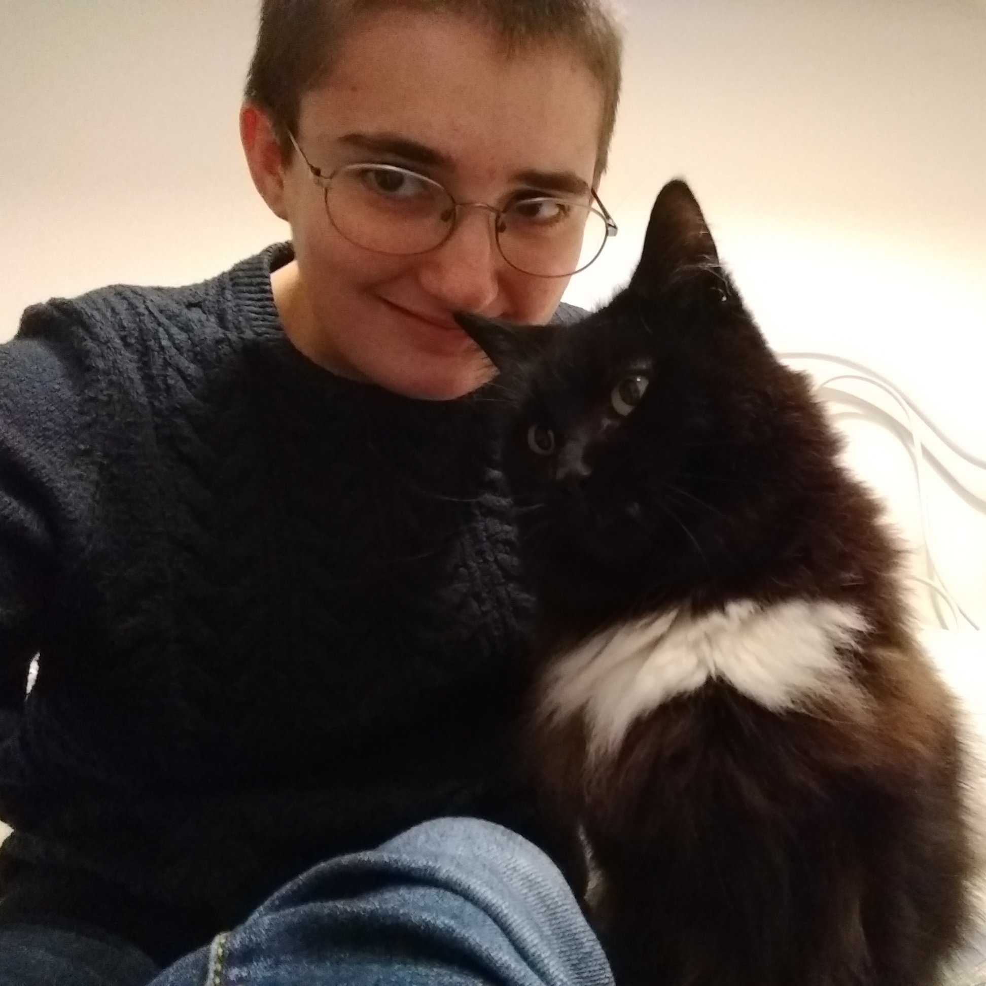 A selfie of me with a gleeful expression, accompanied by a very fluffy black and white cat.