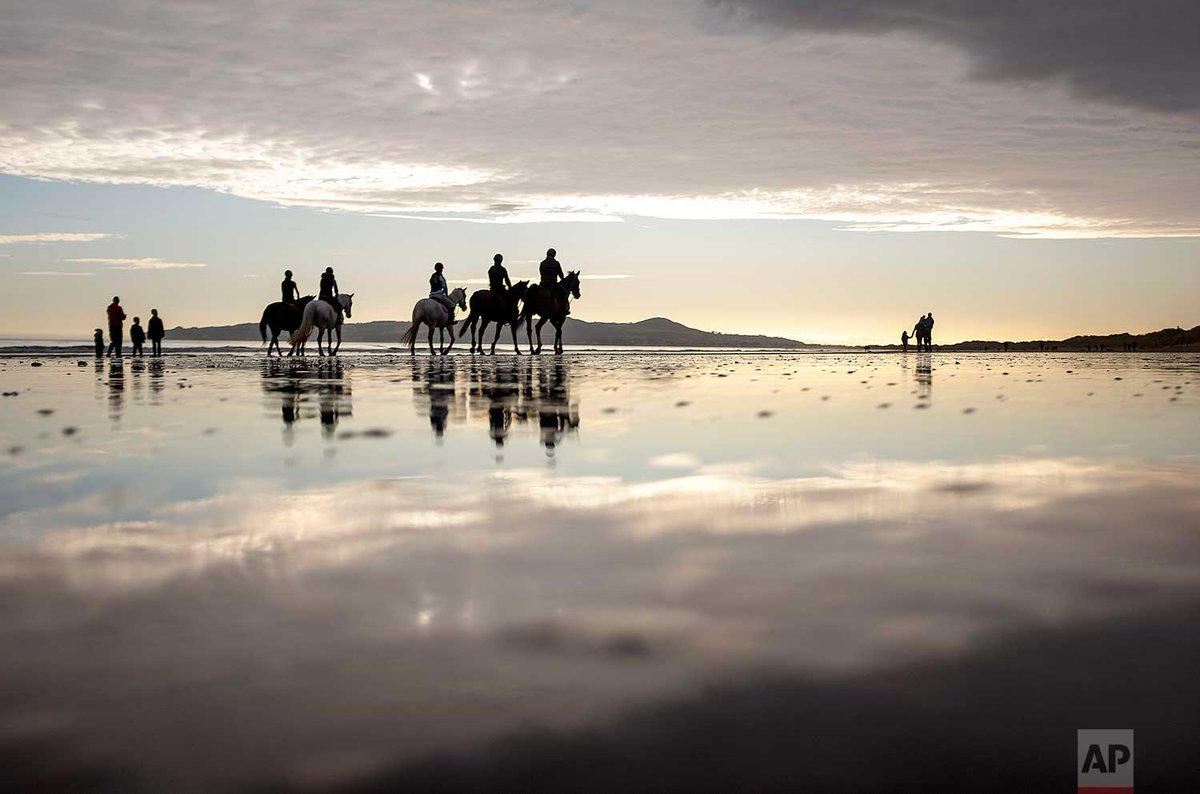 Horses are ridden along the beach today in Portmarnock, County Dublin, Ireland. @DavidGoldmanAP