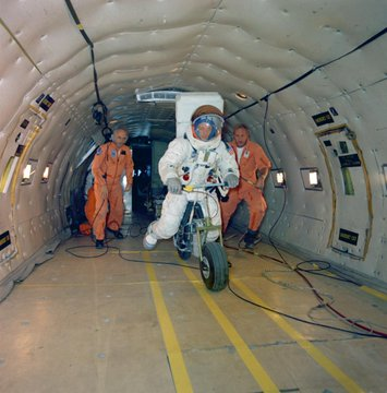 Electric Motor Scooter being tested by an astronaut in a full suit within the fuselage of a KC-135 aircraft.