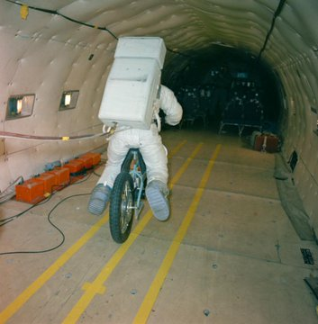 Electric Motor Scooter being tested by an astronaut in a full suit within the fuselage of a C-135 aircraft.