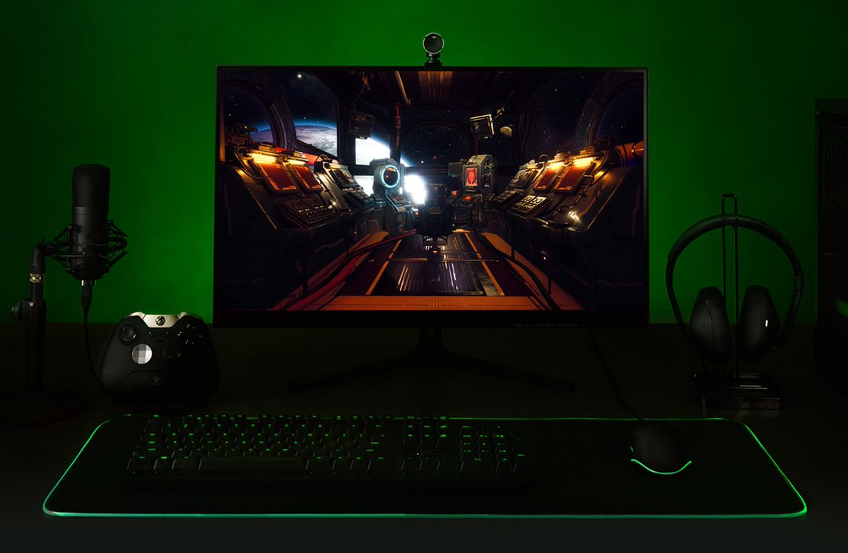 A futuristic PC desktop with green lighting and trim, set against a green background. The screen is displaying The Outer Worlds game for Windows 10.