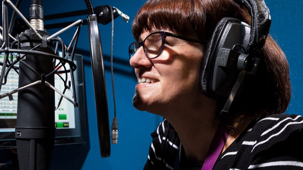 Woman wearing headphones and talking to a microphone.