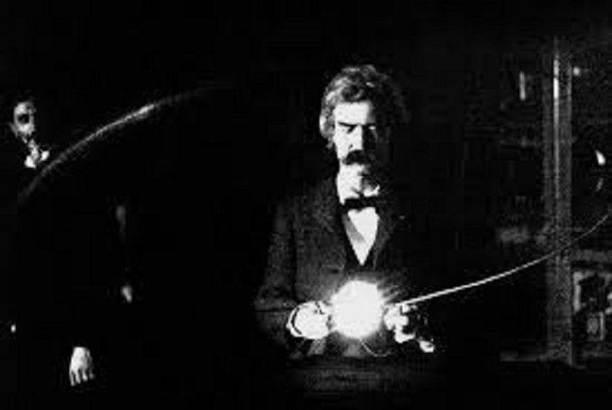 Mark Twain in the lab of Nikola Tesla, spring of 1894. Clemens is holding Tesla's experimental vacuum lamp, which is powered by a loop of wire which is receiving electromagnetic energy from a Tesla coil http://ow.ly/rQGv30oBQp0pic.twitter.com/jJW9o5OhFh