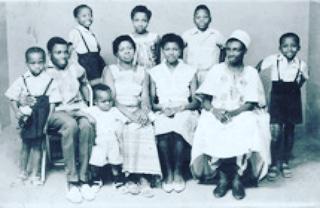 Kano, 1963. Front (L-R): Tony, Paul, Ngozi, Grandma, Chibuzo (my Mum), Oseloka, Ubaka. Back (L-R): Ify, Chineze, Emma. Not in picture: Grandpa, Nduka, Louisa, Medua, Tata.  Grandpa, Paul, Emma, were killed four years later during the #AsabaMassacre.