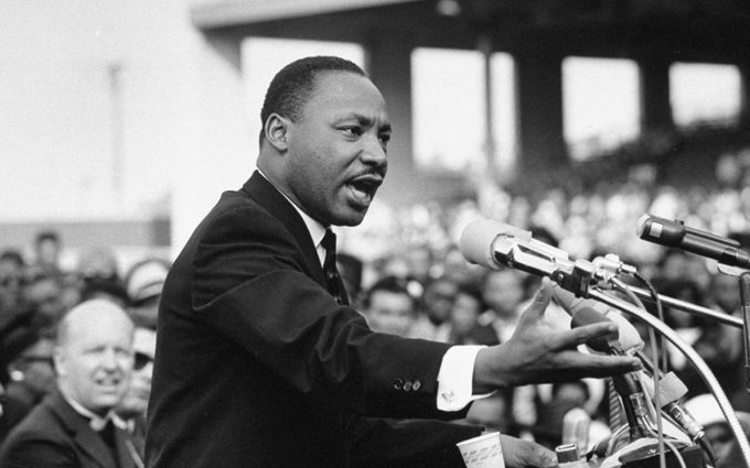 Dr. Martin Luther King, Jr. stands before a podium and microphones and delivers a speech.