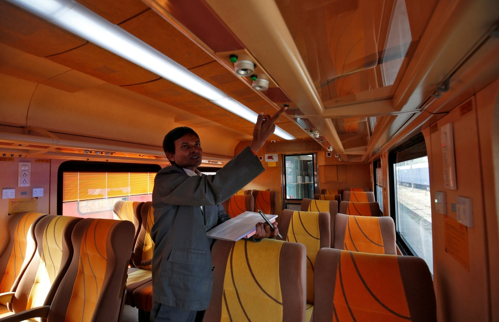 An official shows an overhead panel inside a coach of India's first private train Tejas Express at a railway yard in Ahmedabad.