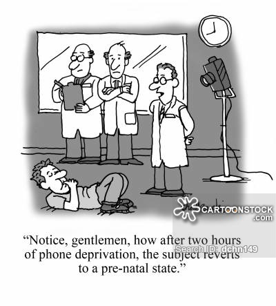 Cartoon of scientists observing their test subject, a man on the floor sucking his thumb. The head scientist notes that the subject has only gone two hours without his phone and already he's reverted to prenatal behavior.