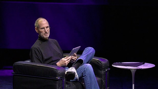 Steve Jobs with ipad in chair.