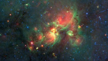 "Newborn stars peek out from beneath their natal blanket of dust in this dynamic image of the Rho Ophiuchi dark cloud from NASA's Spitzer Space Telescope. Called ""Rho Oph"" by astronomers, it's one of the closest star-forming regions to our own solar system, about 407 light-years from Earth."