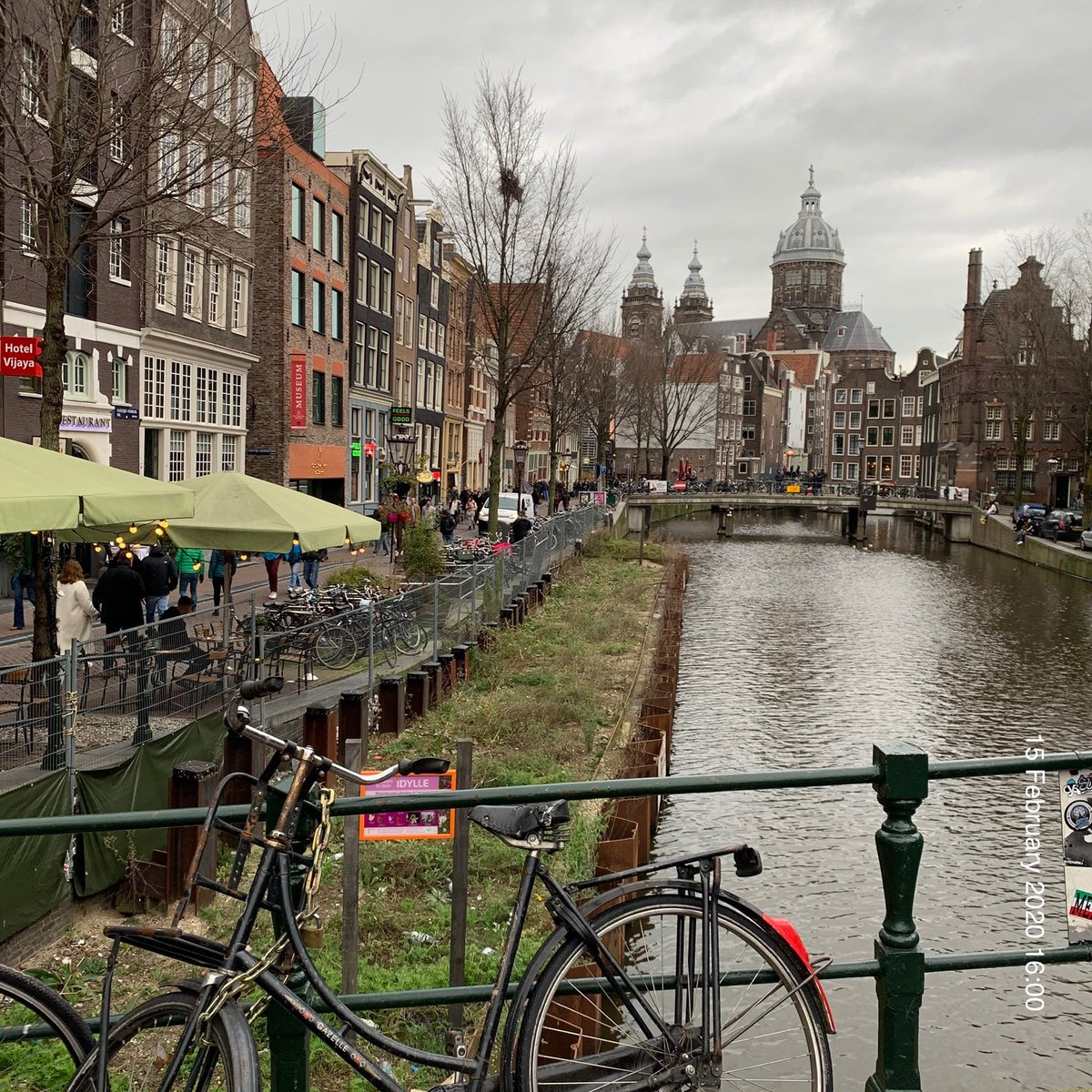 Narrow tilted buildings, canals, & bridges through Amsterdam centrum