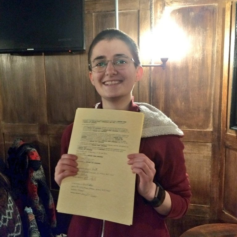 Photo of a short-haired person with glasses (me) holding a signed sheet of paper (my deed poll) and smiling widely.