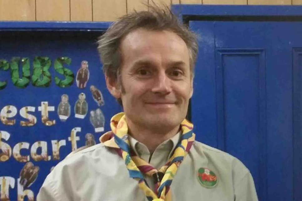 Steve Walsh wears a Scouts uniform featuring two twisted scarves and a beige shirt with badges