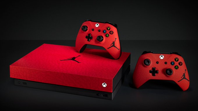 A custom red Limited Edition Nike Jordan Brand Xbox One X and two Xbox One controllers sit on a dark black background.