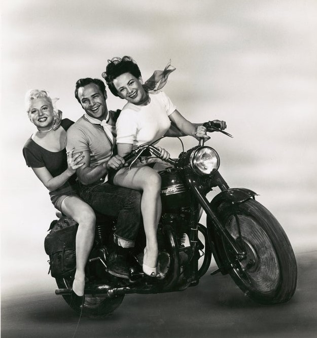 Marlon Brando poses with Mary Murphy and Peggy Maley on a motorcycle to promote 'The Wild One' in 1953. 🎥