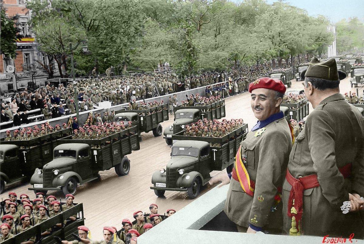 Desfile de la Victoria, Madrid 19 de mayo de 1939. Desde la tribuna de la presidencia, un sonriente general Franco departe con el general Saliquet mientras desfilan los Tercios de Requetés por la Castellana.