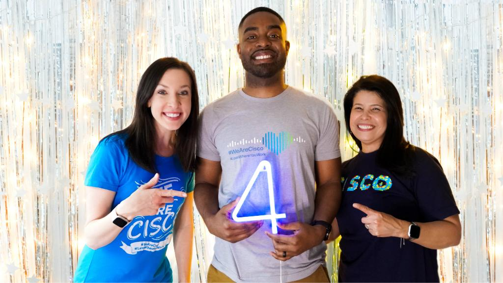 Cisco employees stand next to each other pointing to the number 4 sign.