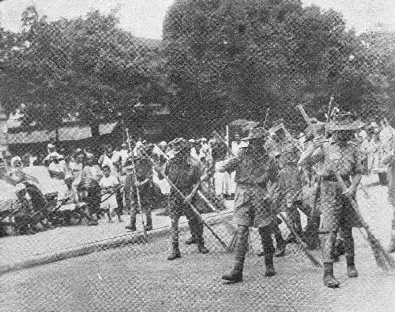 """Japanese conquerors are making Allied prisoners sweep streets of Singapore at gunpoint, as locals gather to watch """"humiliation of the sahibs"""":"""