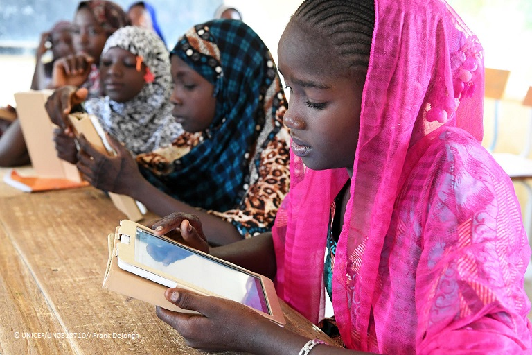 Students with child-friendly tablets provided by UNICEF at a school in #Niger . The tablets, which run on solar power, contain off-line educational content, including from Wikipedia and Khan Academy, adapted to the local context and curriculum.   #ForEveryChild , a digital bridge.