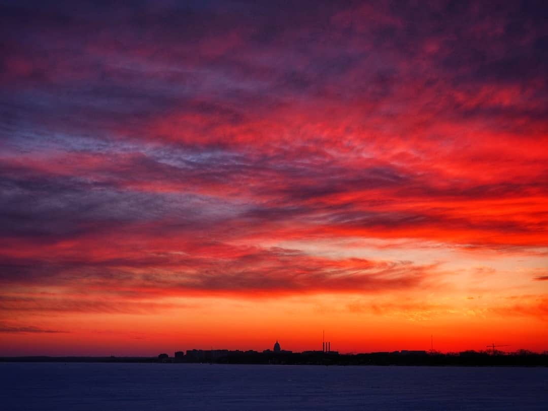 Red and orange clouds over the silhouette of the Wisconsin Capitol and Madison skyline.
