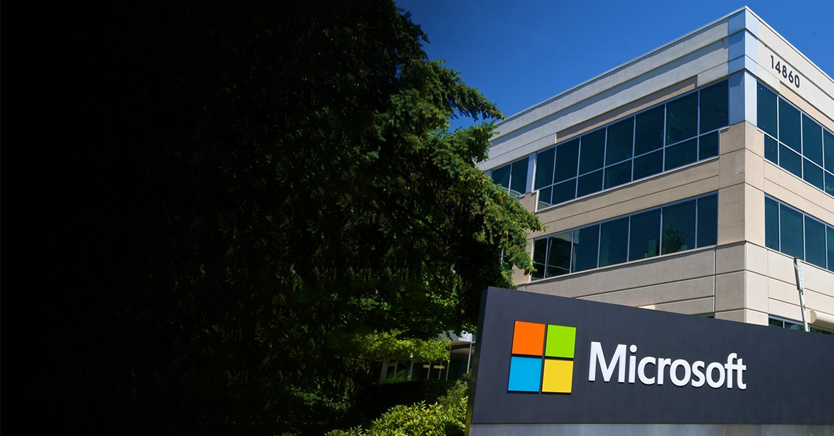 Photography of a Microsoft office building. There is a large Microsoft logo stand in front of the buildiung next to a large green tree. It is a very sunny day with a blue sky.