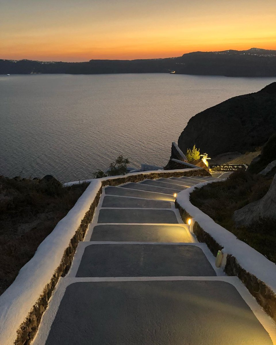 ➡️   Will you take this staircase down towards this striking #sunset in #Santorini! A perfect place to be with your loved one on your #romanticgetaway with #pickyourtrail
