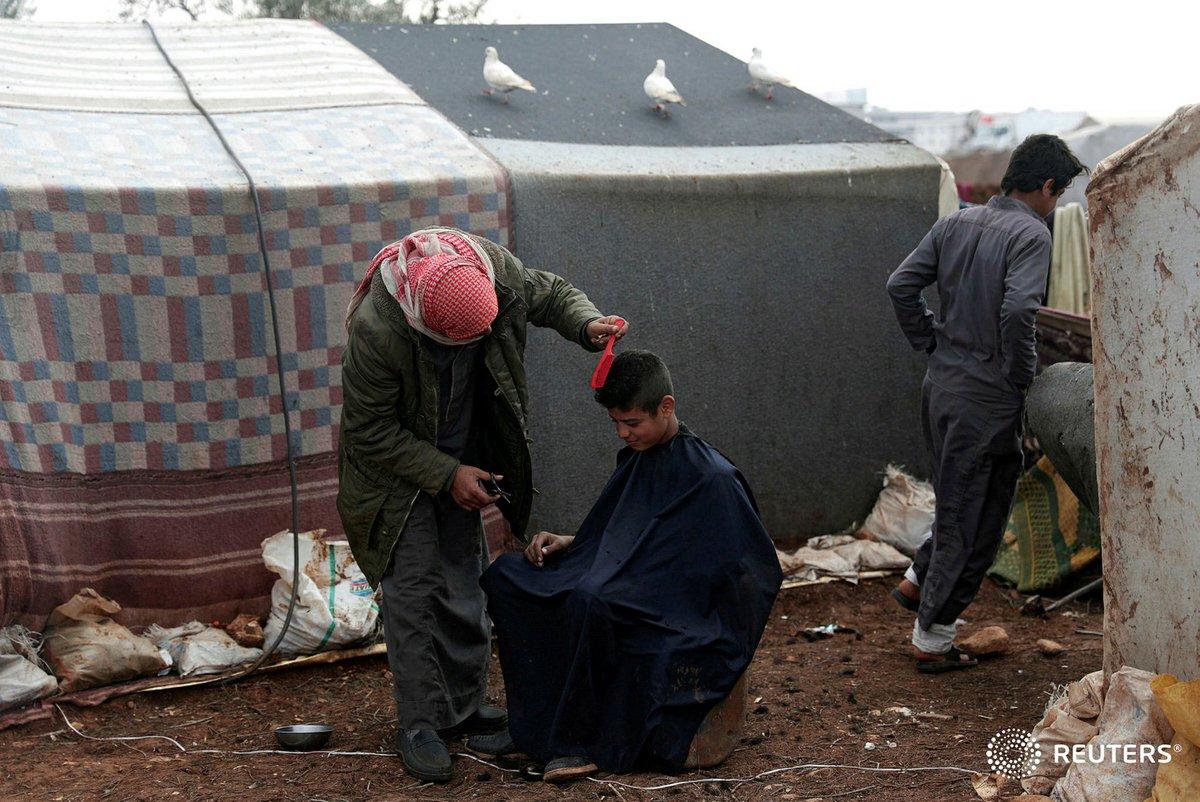 حلاق المخيم اعزاز، ريف #حلب الشمالي #سوريا An internally #displaced youth gets a haircut outside #tents at a makeshift #camp in Azaz, #Syria February 19, 2020.  #REUTERS / #KhalilAshawi  #idlib #saveidlib #war #child #children #savethechildren #photo #photooftheday @reuters