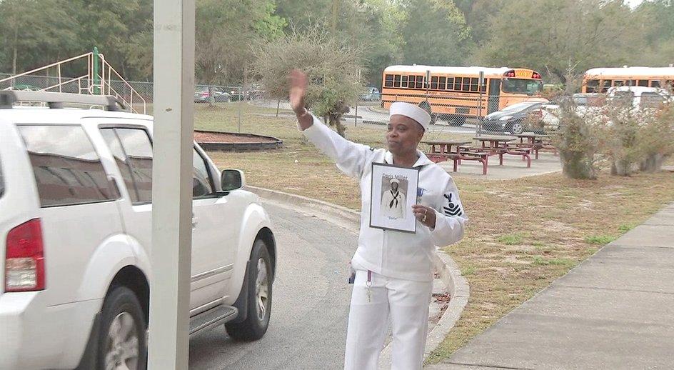 Angela Riley-Maxwel greeting students dressed as Navy Messman Doris Miller.