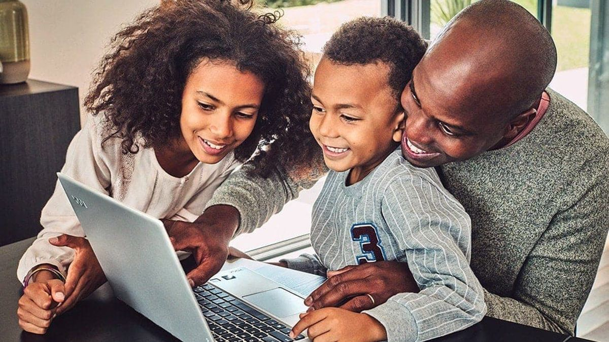 A family of three gathered around a Windows 10 device.