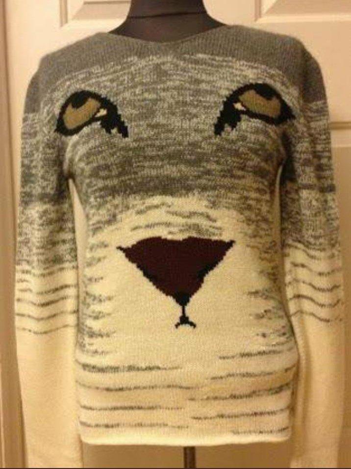 思い出し笑いをしている生物のセーター