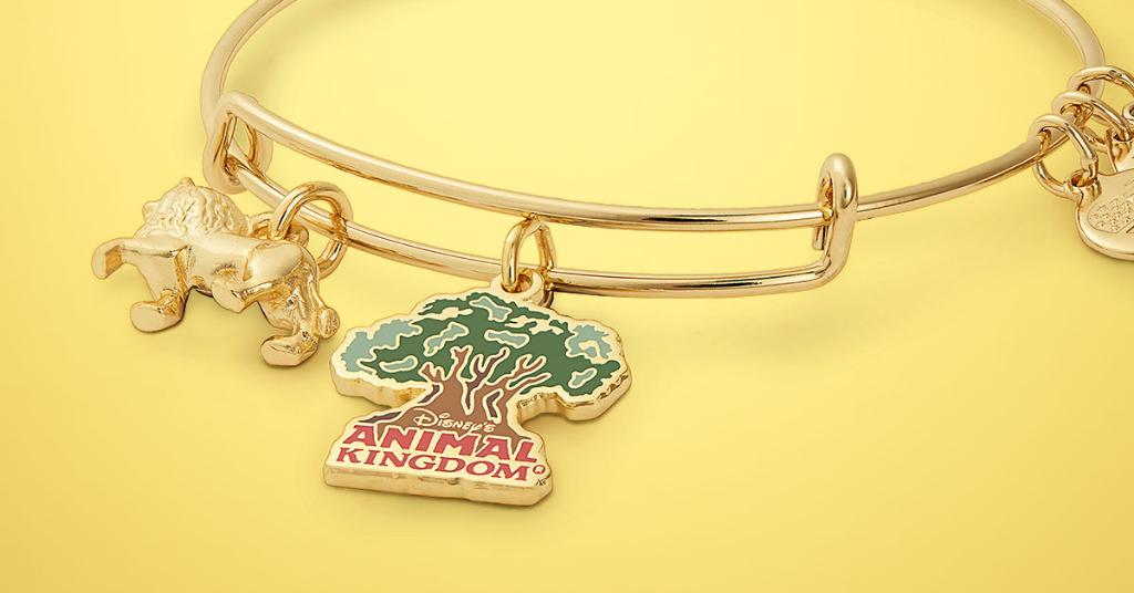 """An Alex & Ani bangle with a lion charm and a charm in the shape of the Tree of Life with """"Disney's Animal Kingdom"""" underneath."""