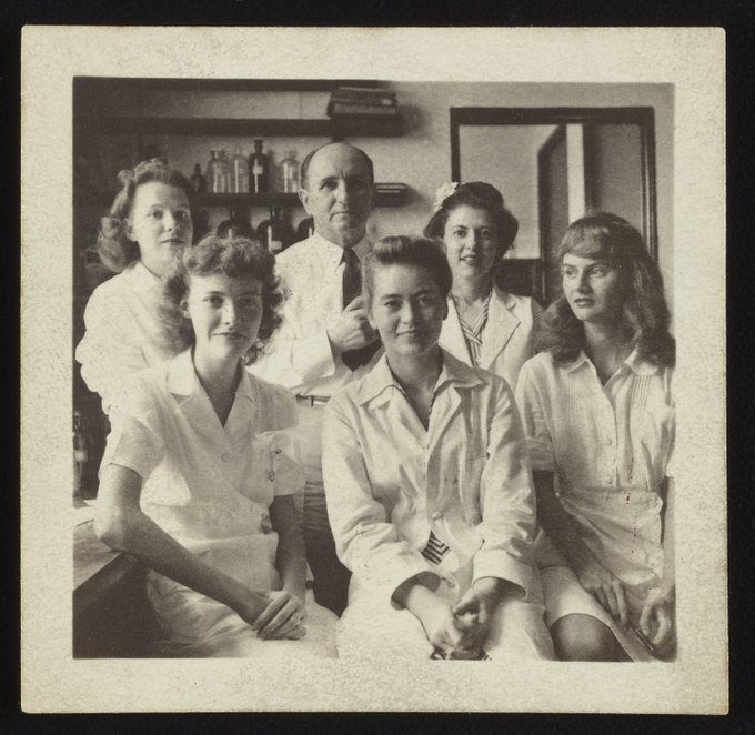 Sepia-toned photo of 5 women and 1 man in a lab. They are all wearing white lab coats.