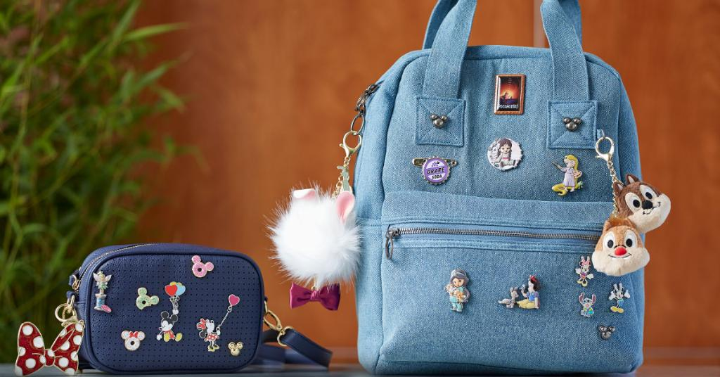 Denim backpack and navy belt bag decorated with new Disney Store Flair pins and charms.