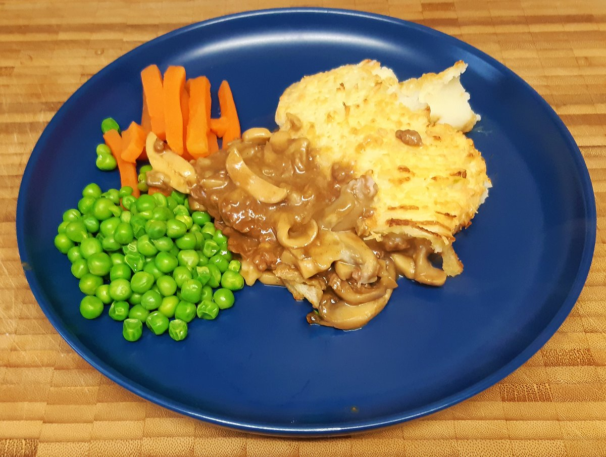 Stewed steak and mushroom with a topping of cheesy mash potato, Carrot batons, peas.
