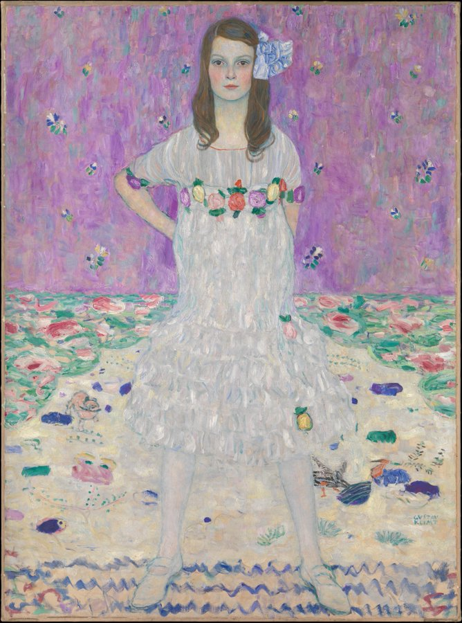 A young girl standing confidently in a white dress against a purple, floral background.