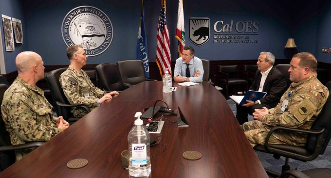 Governor Gavin Newsom sits at a table with military leaders, Cal OES Director Mark Ghilarducci, and Major General David S. Baldwin of the California National Guard.