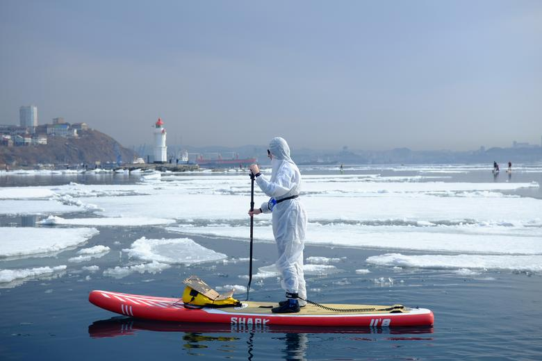 """A sup #surfer wearing a protective suit as a show of support for the people fighting against the spread of coronavirus disease takes part at an annual """"Hijacking an ice floe"""" event marking the opening of the stand up paddle boarding season in #Vladivostok,#Russia.pic.twitter.com/Lq6hEbmXbX"""