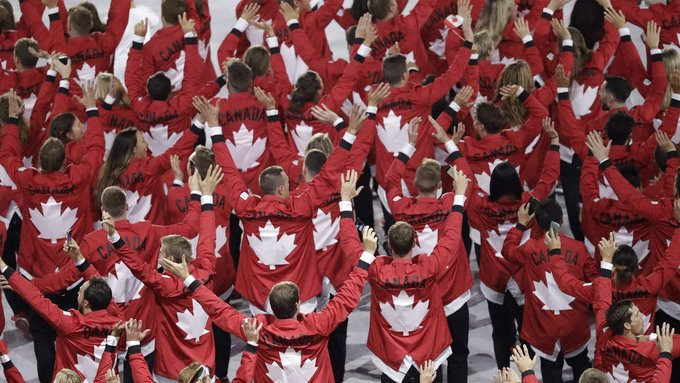 A group of Canadian athletes waving to the crowd.