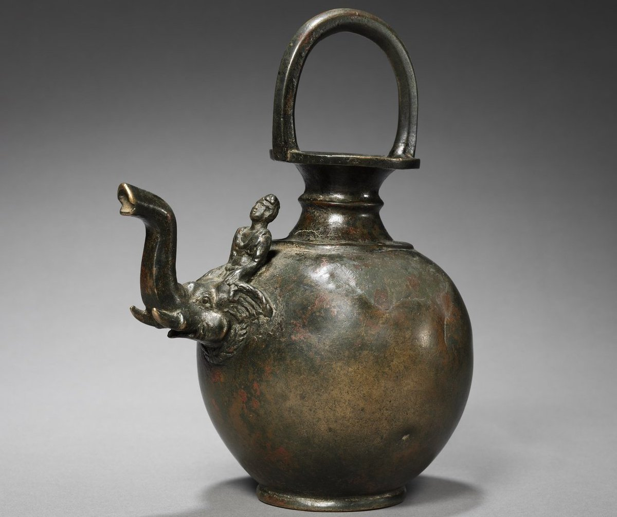 A bulbous shaped ewer with a handle and and narrow neck from Takshashila Dated:~1st century CE The spout which is interesting for it is shaped like an elephant's head with Mahout. Similar door knobs are also seen. Its neck is shaped like hourglass to which a handle is attached.<br>http://pic.twitter.com/KWvWUdrS15