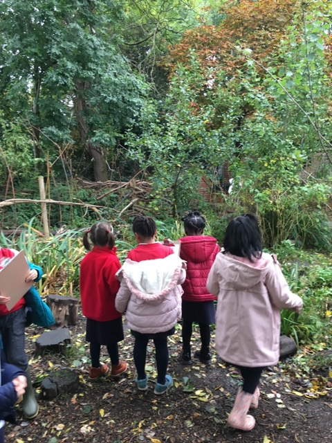 Photo shows four Year 1 children in red school uniform and winter coats, their backs to us as they look at mixed woodland beyond. Photo from Bessemer Grange Primary website http://bessemergrangeprimary.co.uk/1jm/