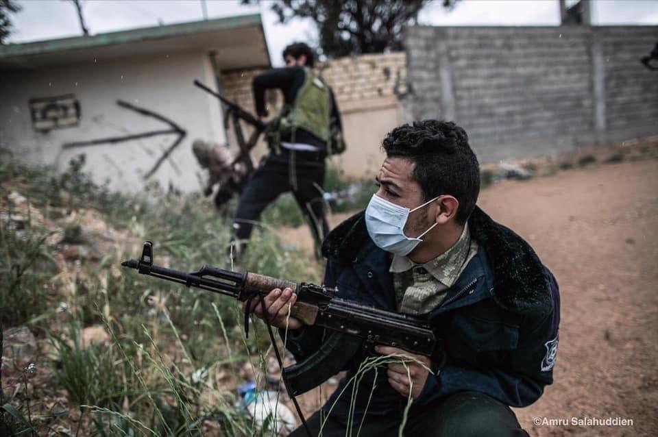 Un combatiente libio en la guerra se protege con mascarilla por la pandemia del coronavirus | Foto de Amru Salahuddien