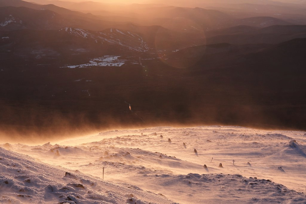 Blowing snow just below the summit cone of work (@MWObs) at sunset earlier this month. The ski resort pictured off yonder is @bretton_woods. #nh #mountains #snow #blowingsnow #sunset