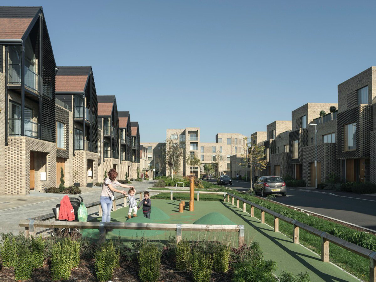 Central carriageway gone, replaced by play space and rain gardens. Narrow service lanes and houses built right up to its edge. Cars parked in integral garages. Huge external spaces as private terraces. At 45dph, nearly all with own street door access. #Buildingforahealthylife