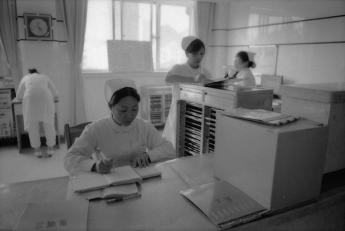 Black and white photograph of four nurses in uniforms working in a hospital in China.