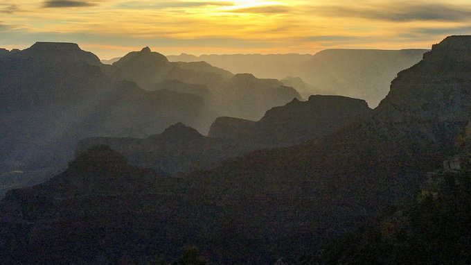 Description: a series of silhouetted ridgelines and promontories bathed in yellow sunrise light.