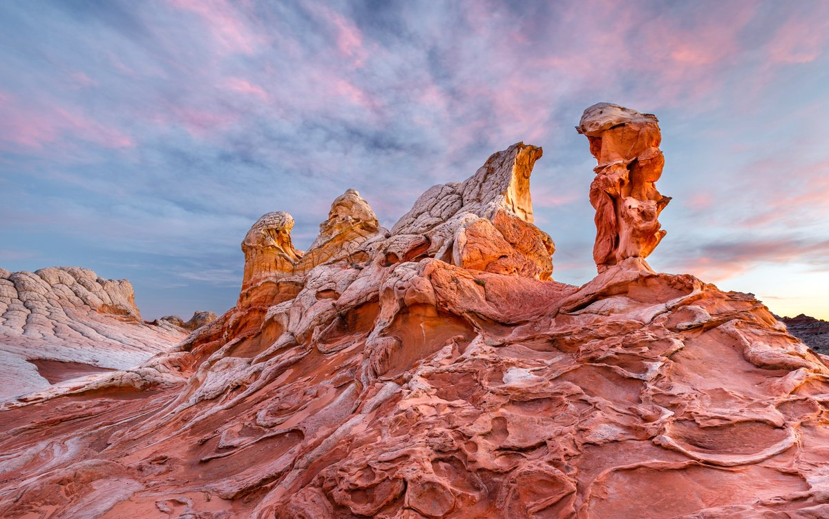 Wispy pink clouds hint at the setting sun behind natural statues at Vermillion Cliffs National Monument. It's a place where rock and sky both swirl with color.   Pic by Jessica Fridrich (http://sharetheexperience.org ) #Arizona