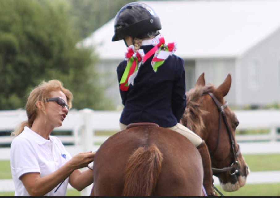 """You locate the ring steward by the out gate, helping a Junior with her stirrups. """"Sorry to interrupt,"""" you say, """"But there's a spectator about to open a parasol right... there!"""" The Steward barks into her walkie-talkie. Seconds later, a volunteer appears next to the spectator."""