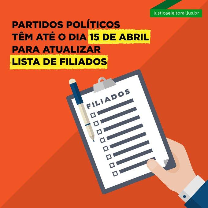 """Fundo laranja, ao centro, a ilustração de um braço a segurar uma prancheta com uma lista, cujo título é """"Filiados"""". Na legenda, """"Partidos políticos têm até o dia de 15 de abril para atualizar lista de filiados""""."""