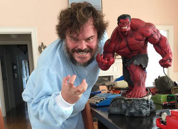 Jack Black posing next to a Red Hulk figurine
