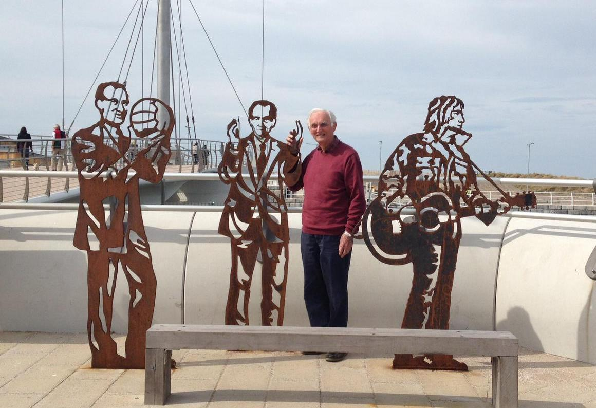 John Houghton standing by seaside sculptures
